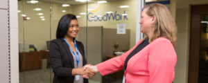 Two businesswomen shake hands in front of the GoodWork Staffing office