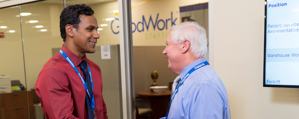 Two businessmen shake hands in front of the GoodWork Staffing office