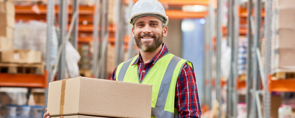 Male warehouse worker carrying boxes